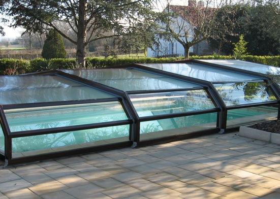 la couleur marron pour l'abri piscine facilite son intégration