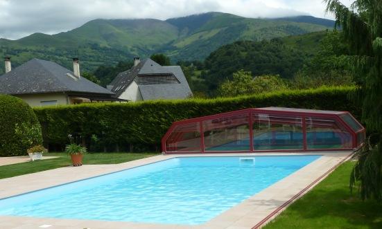 Abri piscine bas rouge rangé en fond de piscine