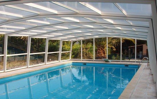 L'abri piscine haut 5 angles olympia a une toiture à facettes très douce.