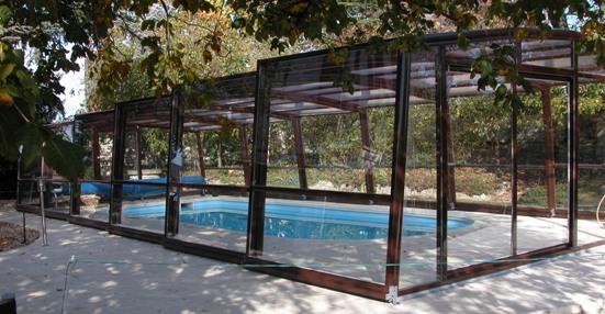 L'abri piscine haut 5 angles olympia s'intègre à merveille dans le paysage et protège la piscine des feuilles